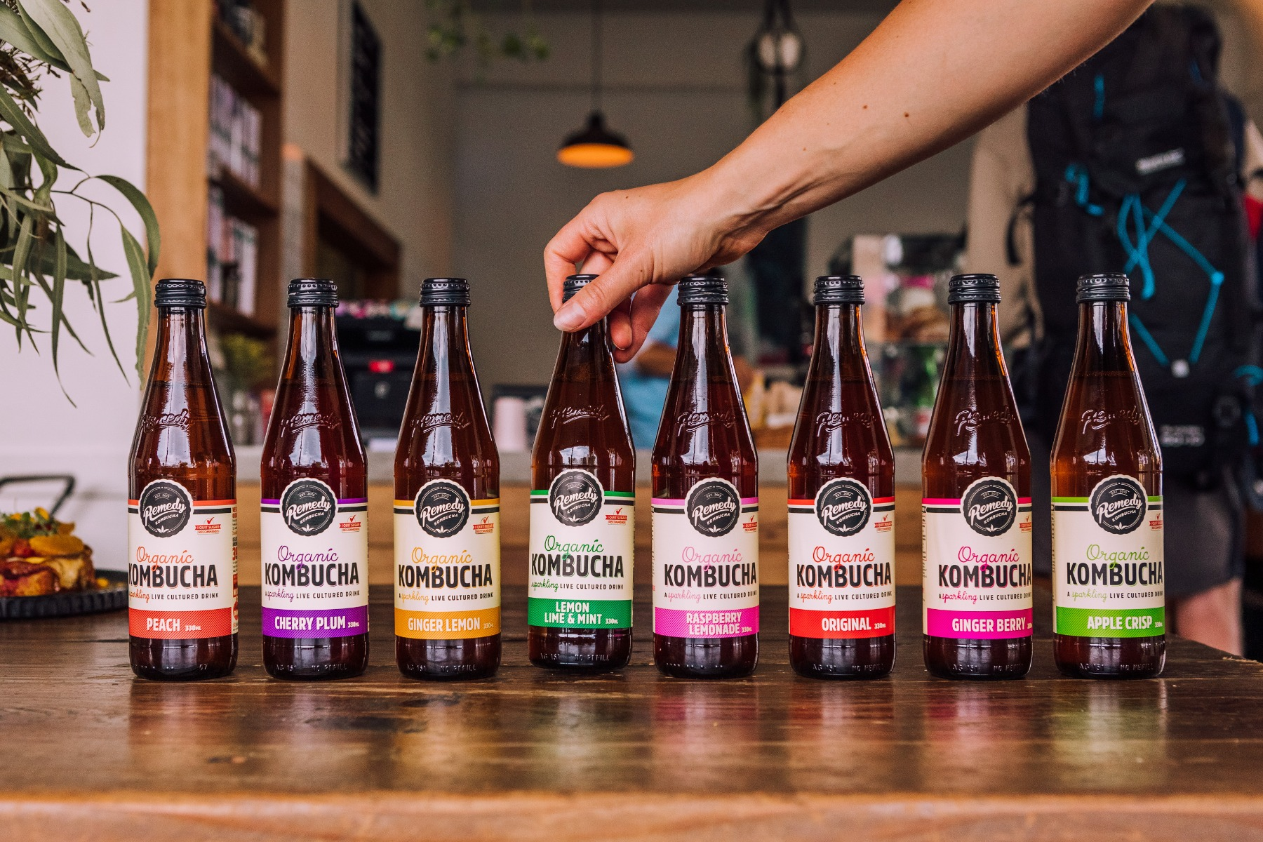 Eight flavours of Remedy Kombucha lined up on a wooden table in a cafe